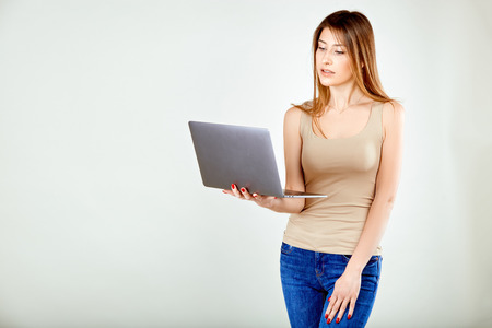 a girl in a beige t-shirt and blue jeans is standing against a gray wall holding a laptop and is looking at his screen in surprise with interest