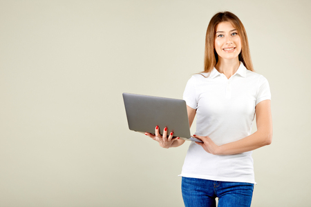 girl in a white polo t-shirt and blue jeans is standing against the gray wall holding a laptop and smiling while looking at the camera Stockfoto