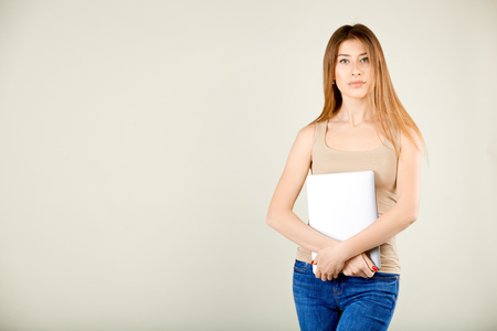 a girl in a beige t-shirt and blue jeans is standing against a gray wall holding a closed laptop in her hands and looking into the camera Stockfoto