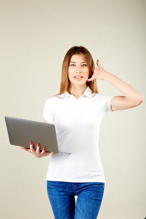 smiling girl in a white polo t-shirt and blue jeans is standing against a gray wall holding a laptop in her right hand and holding her left hand imitating a phone to her ear