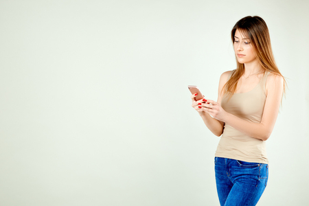 beautiful  girl in a beige T-shirt and blue jeans is standing against a gray wall holding a mobile phone and is looking at his screen with a serious facial expression