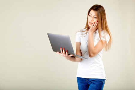 girl in a white polo t-shirt and blue jeans stands against a gray wall holding a laptop in her hand and looks at his screen in surprise