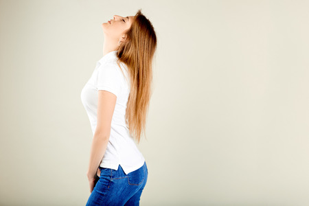 beautiful woman in a white polo t-shirt and blue jeans stands on a gray wall with her head up and eyes closed