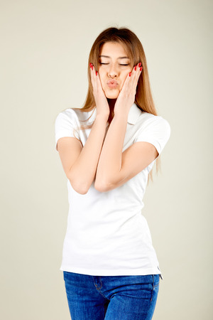 girl with closed eyes in a white polo shirt and blue jeans stands against a gray wall puffed out her cheeks and holds her hands on them