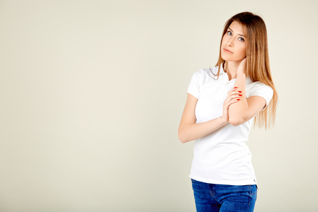 beautiful woman in a white polo t-shirt and blue jeans stands against a gray wall and looks thoughtfully