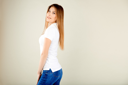 beautiful woman in a white polo t-shirt and blue jeans stands against a gray wall and looks on you smiling with open mouth