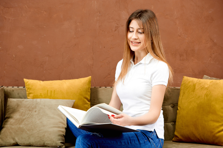 woman in a white polo t-shirt and blue jeans is sitting on a brown sofa against a brown wall and reading a book smiling
