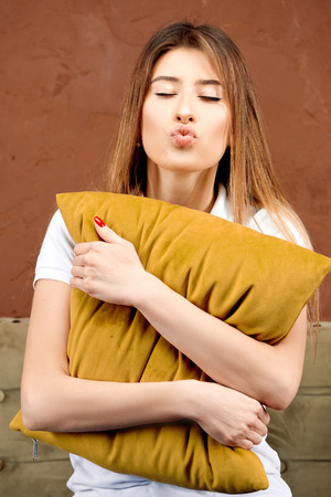 a girl in a white polo shirt and blue jeans sits on a brown sofa against a brown wall holding a pillow in her hands and presents how she kisses someone Stockfoto