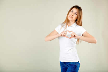 beautiful woman in a white polo t-shirt and blue jeans stands against a gray wall smiling from happiness and folded her fingers in the shape of a heart Stockfoto