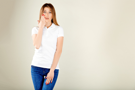 woman in a white polo t-shirt and blue jeans stands against a gray wall holding her right hand to her face and looks surprised Stockfoto