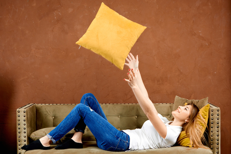 girl in a white polo t-shirt and blue jeans is lying on a brown sofa against a brown wall throws a pillow up and smiling with happiness Stockfoto