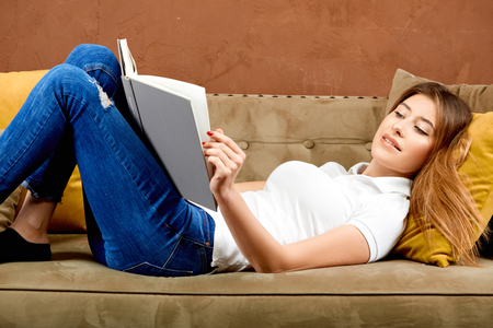 woman in a white polo t-shirt and blue jeans is lying on a brown sofa against a brown wall and reading a book smiling