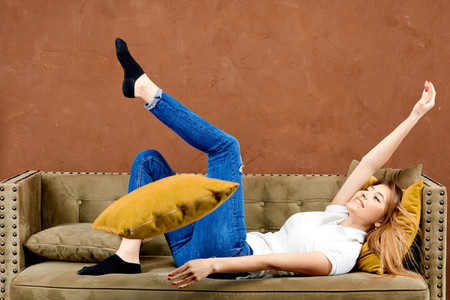 girl in a white polo t-shirt and blue jeans is lying on a brown sofa against a brown wall and smiling with happiness