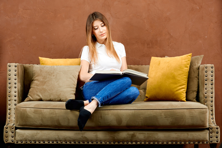 serious woman in a white polo t-shirt and blue jeans is sitting on a brown sofa against a brown wall and reading a book