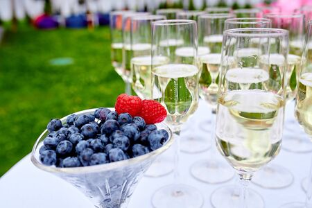 blueberries with raspberries stand in a glass in the background chilled champagne spilled in crystal tall glasses against a background of green grass Stock Photo