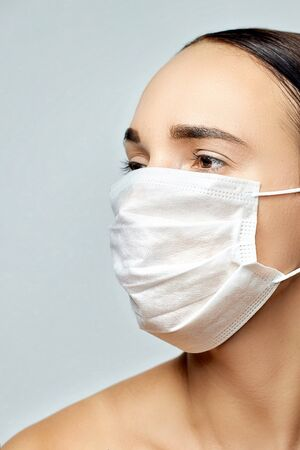 young beautiful brunette with brown eyes in a white disposable medical mask looks in his right side without clothes on a gray background