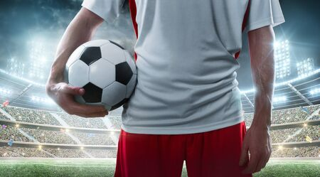 Soccer player holding soccer ball on the stadium Close up