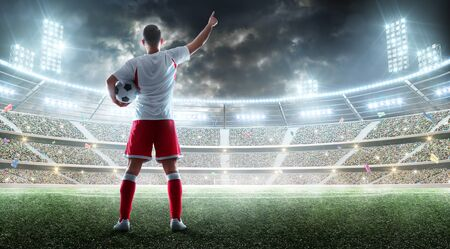 Il calciatore tiene un pallone da calcio sullo stadio professionale Archivio Fotografico