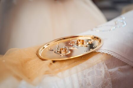silver metal: Vintage photo of wedding rings on a tray with water drops