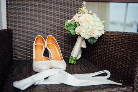 wooden bed: close-up of bridal bouquet of roses, wedding flowers for the ceremony on the bed in a hotel room with white shoes