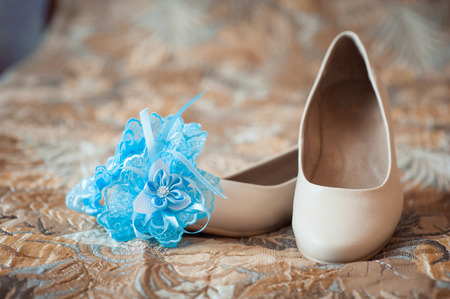 foot gear: beautiful white shoes from bride with garter Stock Photo