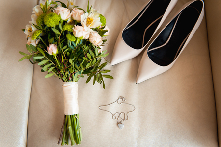romance rose: close-up of bridal bouquet of roses, wedding flowers for the ceremony on the bed in a hotel room with white shoes