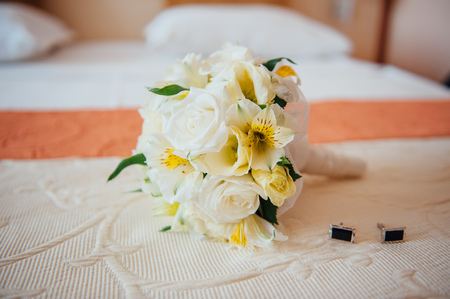 bedspread: Colorful bridal bouquet with male studs on the bedspread Stock Photo