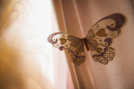 window curtains: artificial butterfly on window curtains close up