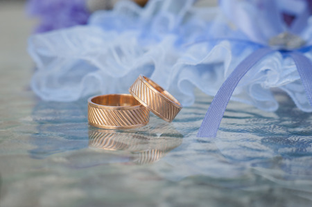 booked: A pair of  wedding rings with bokeh background blue garter Stock Photo