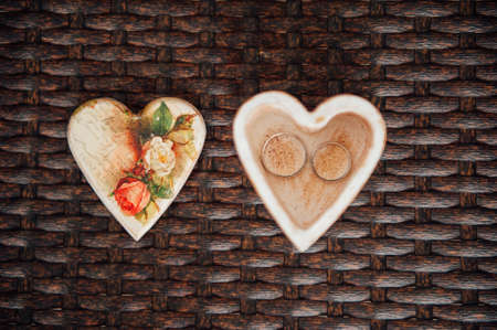 booked: pair of wedding rings in a wooden box in the shape of heart Stock Photo