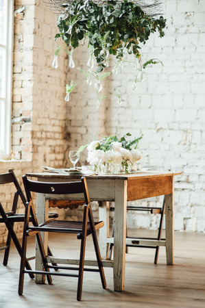 Wedding room decorated loft style with a table and other accessories candles , peonies , bulbs , bricks , window