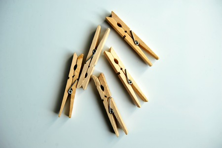 consolidate: wooden clothespins on the white background. with slight shadow