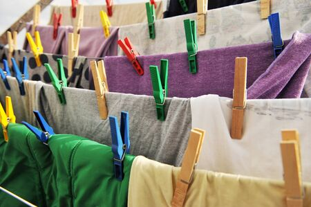 laundered: Close-up of colorful laundry pins and hanged clothes drying.