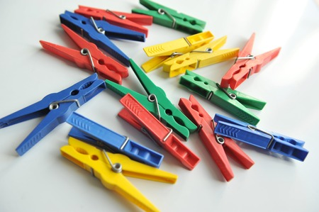 multicoloured: Multi-coloured clothespins scattered randomly on the white background.