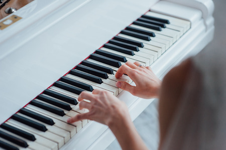 avocation: Close up of hands playing white piano. Concept of music and entertainment.