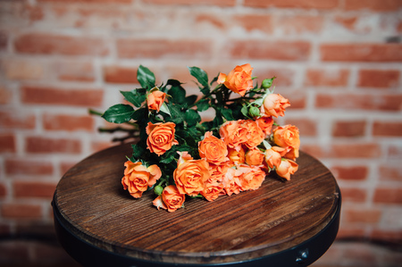studio background: Mini roses on vintage wooden surface near brick wall