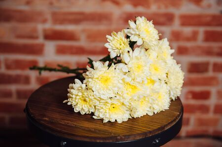 daisy stem: bouquet of chrysanthemums on a wooden plate.