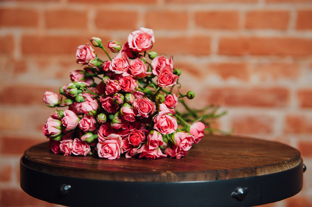 room background: Mini roses on vintage wooden surface near brick wall