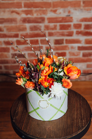 daisy stem: basket of spring flowers on a wooden chair. handmade. Stock Photo
