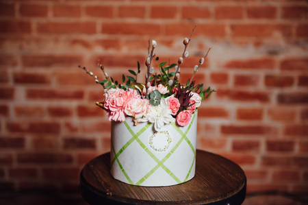 daisy: basket of spring flowers on a wooden chair. handmade. Stock Photo