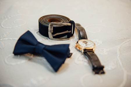 suede belt: Set of groom clothes. Wedding rings, shoes, cufflinks and bow tie detalis fashion Stock Photo