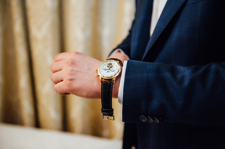 clasping: groom clasping stylish watch band on his wrist.