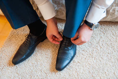 young  cuffs: A young man tying elegant shoes indoors. Stock Photo