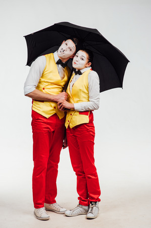 funny guys: studio shot of two mimes isolated on a white background. with umbrella Stock Photo