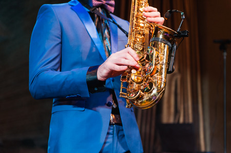 saxophonist: Saxophone player jazz music instrument Saxophonist with Baritone sax closeup on black