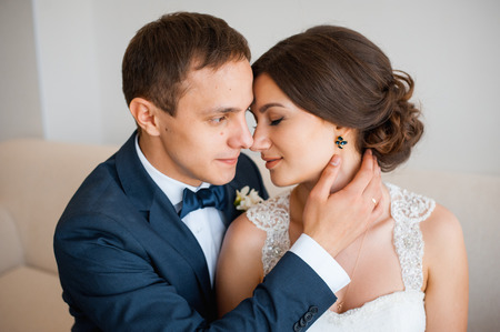 cute guy: Wedding couple indoors is hugging each other. Beautiful model girl in white dress. Man in suit. Beauty bride with groom. Female and male portrait. Woman with lace veil. Cute lady and handsome guy