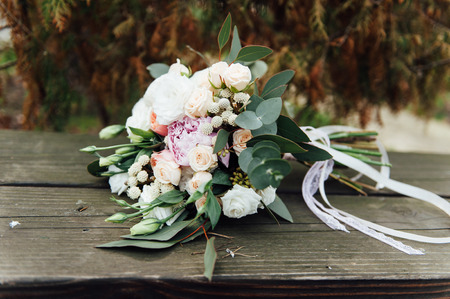 Bridal bouquet of roses on a  brown wooden planks