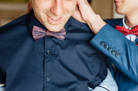 formal dressing: Happy friends helps stylish groom getting ready for his wedding day