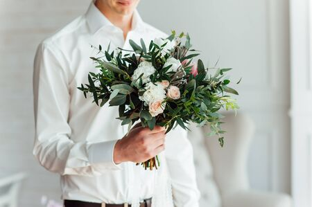 red hand: Beautiful wedding bouquet in hands of the groom. Stock Photo