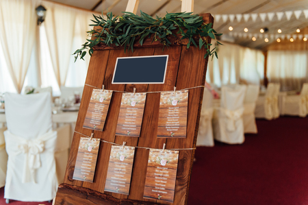 wedding table decor: Original vintage wooden board with decoration and ribbons and a guest list, heart and bucket in the background. with a place for an inscription